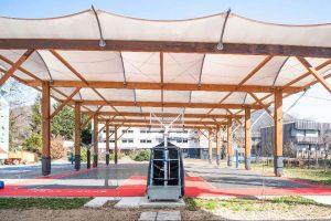 Construction d'un terrain de basket couvert avec charpente mixte bois lamelle colle et acier galvanise et couverture en membrane textile, a Voiron (38)